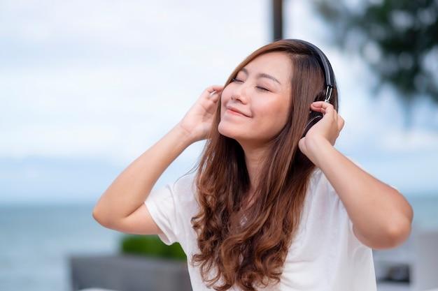 Eine schöne asiatische frau, die musik mit kopfhörer hört, während sie am meer sitzt