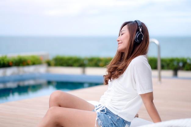 Eine schöne asiatische frau, die musik mit kopfhörer hört, während sie am schwimmbad sitzt