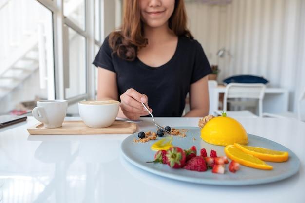 Eine schöne asiatische frau, die orangenkuchen mit gemischten früchten durch löffel im café isst