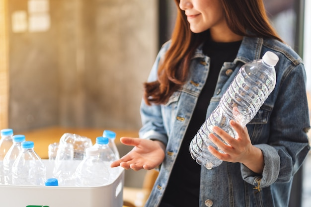 Eine schöne asiatische frau, die recycelbare müllplastikflaschen in einem mülleimer zu hause hält und sammelt
