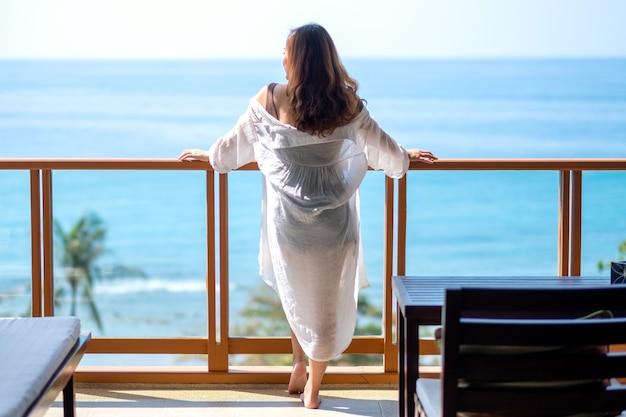 Eine schöne asiatische frau, die steht und den meerblick auf dem balkon genießt?