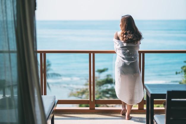 Eine schöne asiatische frau, die steht und genießt, den meerblick auf balkon zu beobachten