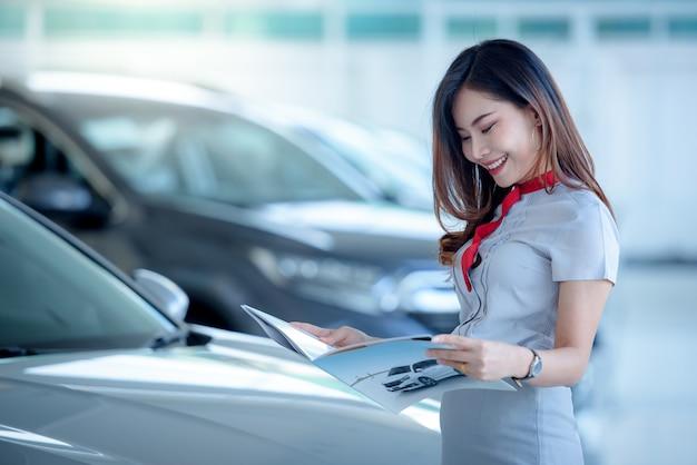 Eine schöne asiatische frau, ein neues autodokument mit interesse betrachtend, um ein neues auto zu kaufen
