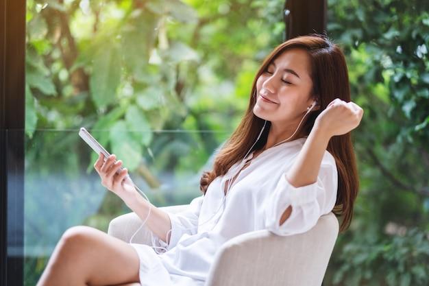 Eine schöne asiatische frau genießen musik mit telefon und kopfhörer zu hause, grüne natur, glück und entspannung konzepte