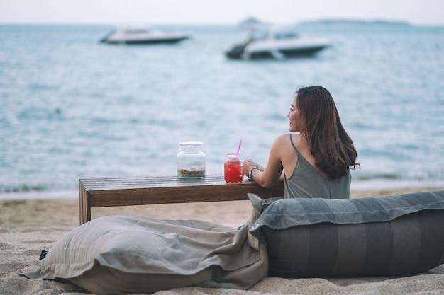 Eine schöne asiatische frau genießt es, am strand am meer zu sitzen und zu entspannen