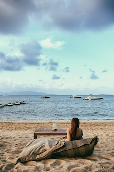 Eine schöne asiatische frau genießt es, am strand am meer zu sitzen