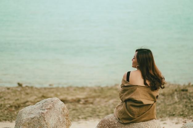 Eine schöne asiatische frau genießt es, auf dem felsen an der küste zu sitzen