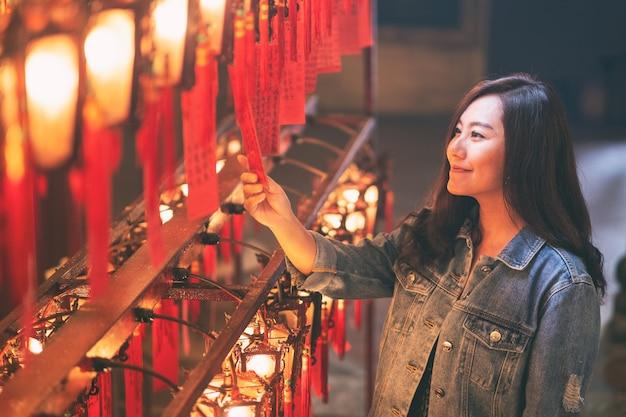 Eine schöne asiatische frau genoss es, rote lampen und wünsche im chinesischen tempel zu betrachten