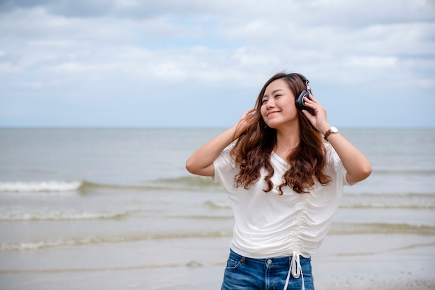 Eine schöne asiatische frau hört gerne musik mit kopfhörer am meer