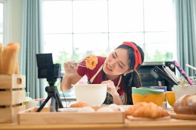 Eine schöne asiatische frau macht bäckerei, live-streaming oder nimmt videos in sozialen medien in ihrem haus auf