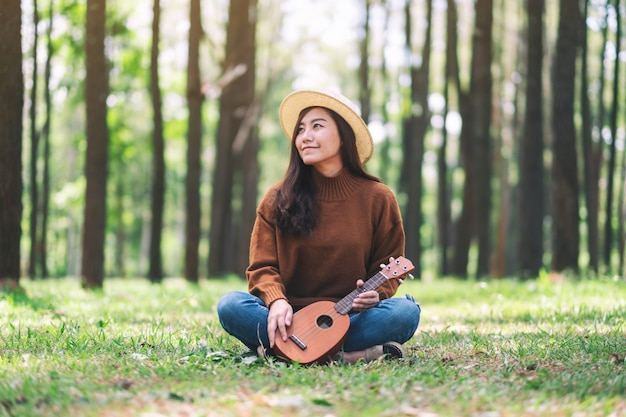 Eine schöne asiatische frau sitzt und spielt ukulele im park