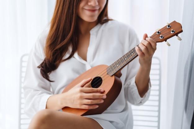 Eine schöne asiatische frau sitzt und spielt ukulele im schlafzimmer