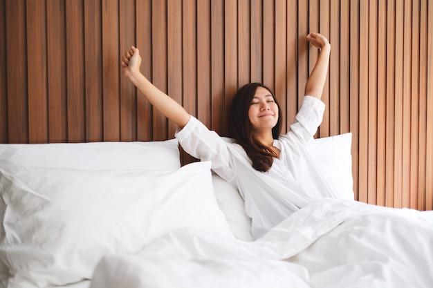 Eine schöne asiatische frau streckt sich, nachdem sie morgens auf einem weißen gemütlichen bett zu hause aufgewacht ist