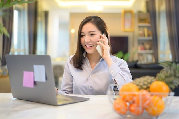 Eine schöne asiatische geschäftsfrau arbeitet zu hause mit ihrem computer.