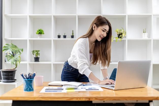 Eine schöne asiatische geschäftsfrau, die in einem raum steht, sie unterhält sich mit ihrem partner über einen laptop-messenger, sie ist eine weibliche führungskraft eines startup-unternehmens. konzept des finanzmanagements