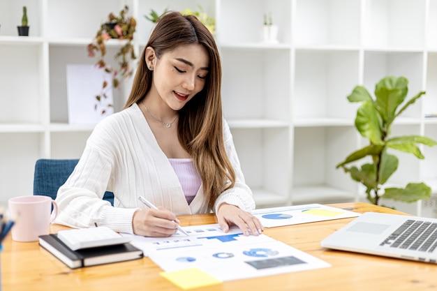 Eine schöne asiatische geschäftsfrau, die in ihrem privaten büro sitzt, sie überprüft die finanzdokumente des unternehmens, sie ist eine weibliche führungskraft eines startup-unternehmens. konzept des finanzmanagements.