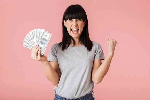 Eine schöne aufgeregte junge frau posiert isoliert über rosa wand mit geld.