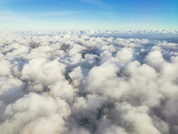 Eine schöne aussicht vom flugzeug auf weiße, voluminöse, flauschige gewitterwolken und den raum der stratosphäre, draufsicht.