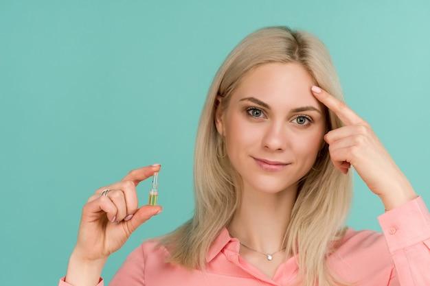 Eine schöne bloggerin zeigt einen finger im gesicht und hält eine ampulle