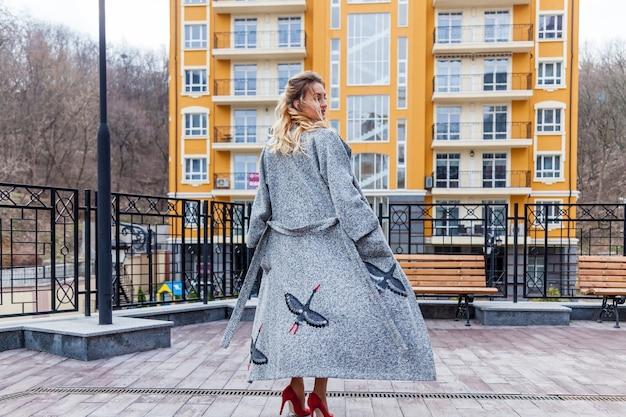Eine schöne blonde frau in einem grauen mantel mit stickmuster. die frau posiert auf dem balkon mit einem dekorativen zaun auf einem städtischen hintergrund.