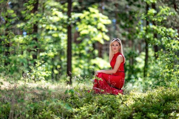 Eine schöne blonde frau in einem roten langen kleid sitzt auf einem baumstumpf im wald.