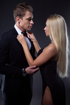 Eine schöne blonde frau in einem schwarzen abendkleid passt die fliege ihres eleganten lieblingsmannes an