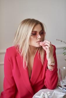 Eine schöne blonde frau in einer rosa jacke sitzt am tisch und isst makronenkekse