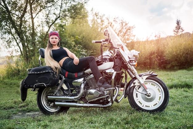 Eine schöne blonde frau sitzt auf einem motorrad
