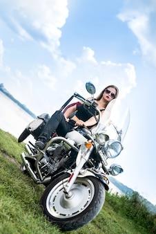 Eine schöne blonde frau sitzt auf einem motorrad Premium Fotos