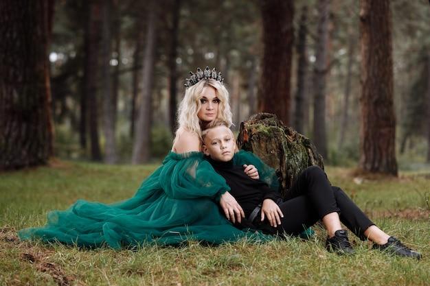 Eine schöne blonde junge frau in einem langen grünen kleid und einem diadem auf ihrem kopf mit stilvollem kleinen sohn im wald.