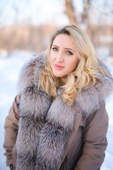 Eine schöne blondine in einem pelzmantel mit pelzkragen steht in einem winterpark