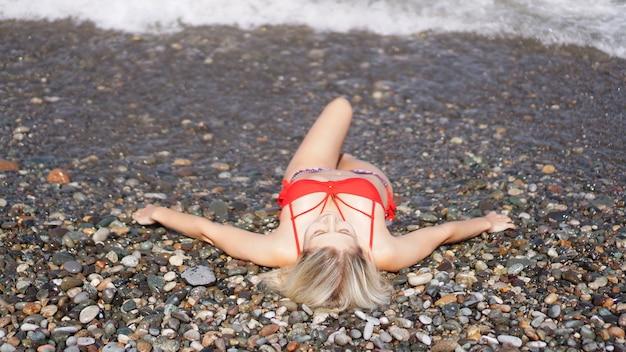 Eine schöne blondine in einem roten badeanzug sonnt sich an einem kiesstrand in der nähe des meeres. sie genießt die sonne. sie liegt mit ausgestreckten armen da