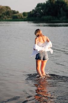 Eine schöne blondine steht mit dem rücken zum sonnenuntergang, eine junge frau in weißer kleidung und jeans ...