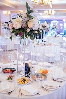 Eine schöne blumenvase auf einem tisch in einem luxusrestaurant. hochzeitsdekorationen
