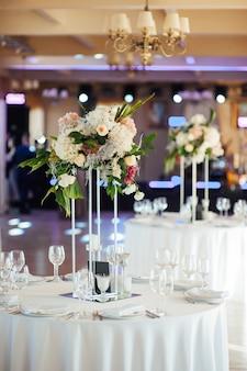 Eine schöne blumenvase auf einem tisch in einem luxusrestaurant. hochzeitsdekorationen.