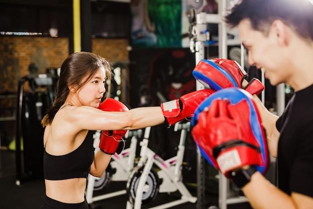 Eine schöne braunhaarige asiatische frau, die das boxen mit einem asiatischen männlichen trainer übt.