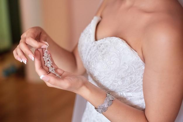 Eine schöne braut in einem langen kleid im hotel und warten auf den bräutigam. juwelen der braut