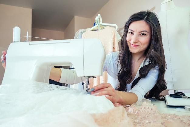 Eine schöne brünette näherin mit langen haaren arbeitet mit einer nähmaschine. schneider mit schaufensterpuppe im studio. junge modedesignerin, die ein kleid näht