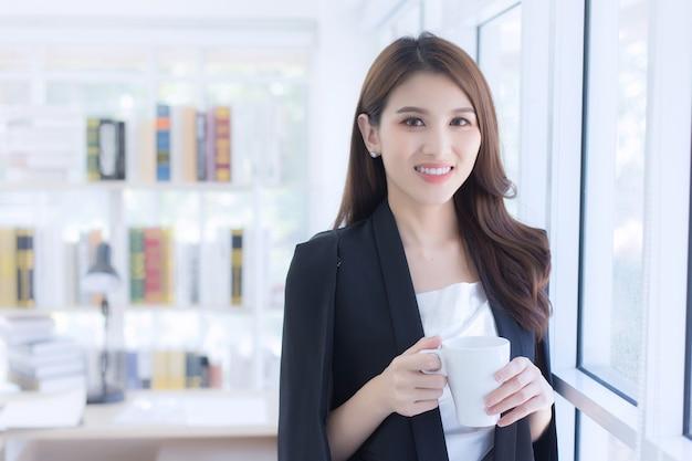 Eine schöne bürodame, die eine kaffeetasse am fenster hält und glücklich am arbeitsplatz steht