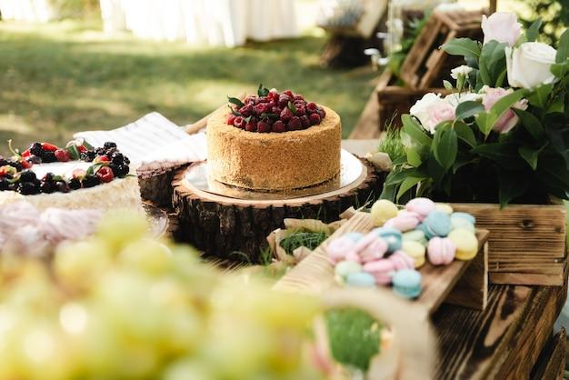 Eine schöne dekoration des hochzeitsbuffets im freien mit süßigkeiten