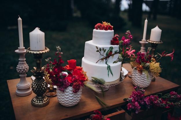 Eine schöne dreistufige hochzeitstorte, dekoriert mit vogel, rosa blumen und zweigen mit grünen blättern in einem rustikalen stil. festliches dessert. hochzeitskonzept.