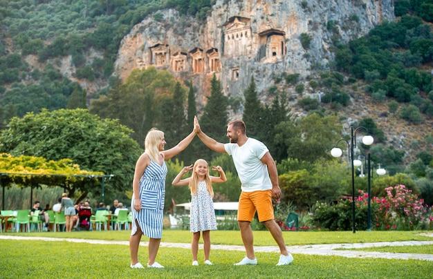 Eine schöne familie steht auf dem hintergrund eines berges in der stadt dalyan. menschen in der nähe lykischer gräber in der türkei