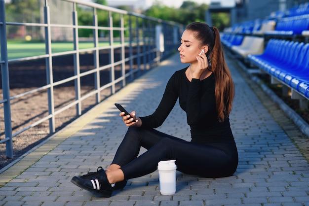 Eine schöne fitnessfrau in schwarzer sportbekleidung benutzt telefon und hört nach dem training musik auf der stadiontribüne. sport und gesundes konzept.