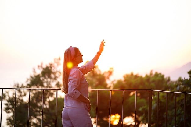 Eine schöne frau bei sonnenuntergang steht auf einer terrasse mit blick auf das meer. foto in hoher qualität