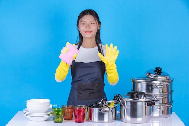 Eine schöne frau beim abwasch vor ihm auf einem blauen hintergrund.