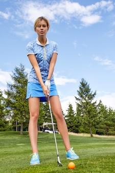 Eine schöne frau beim golfspielen wird fertig, den ball vor dem loch auf einem grünen feld zu schlagen. das golfspiel, das streben nach exzellenz, persönliche exzellenz, königlicher sport