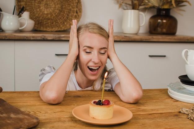Eine schöne frau betrachtet einen kuchen mit einer kerze und freut sich über das geburtstagskonzept