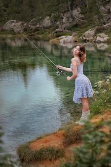Eine schöne frau, die auf dem see fischt