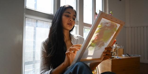 Eine schöne frau, die auf leinwand mit pinsel malt, während sie am modernen und bequemen holzboden des kunststudios sitzt konzept der arbeitenden künstlerfrau.