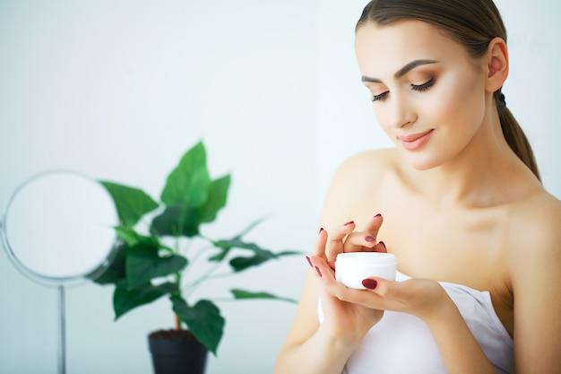 Eine schöne frau, die ein hautpflegeprodukt, eine feuchtigkeitscreme oder eine lotion und eine hautpflege verwendet, die um ihrem trockenen teint sich kümmern. feuchtigkeitscreme in weiblichen händen